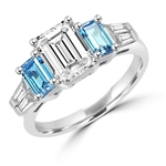 Classic Wide Ring with a 2 Ct. Emerald Cut Brilliant Masterpiece in the center, saluted on each side by a 0.5 ct. Emerald Cut Aquamarine Stone and clear white Baguette Masterpieces further down. 3.5 Cts. T.W, in Platinum Plated Sterling Silver.