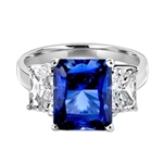 Sapphire Ring - 4.0 Cts. Radiant Emerald cut Saphhire Essence in center accompanied by Radiant Emerald cut Diamond Essence on sides. 5.0 Cts. T.W. set in Platinum Plated Sterling Silver.