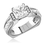 Designer Ring with 2.0 Cts. Princess Cut Diamond Essence in center and baguettes and melee on sides set in Platinum Plated Sterling Silver. Available in select Ring sizes.