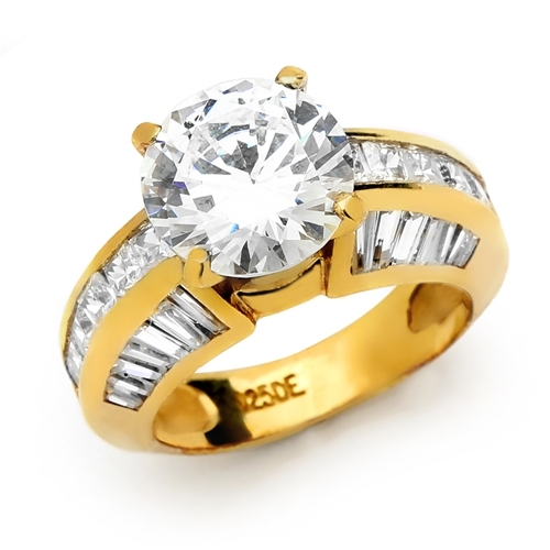 Diamond Essence Designer Ring with 3.50 Cts. Round Brilliant Center, set off by Chanel set Princess stones and Tapered Baguettes on either side.5.50 Cts. T.W. set in 14K Gold Vermeil.