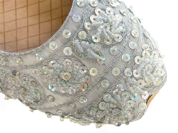 Light silver silk Indian khussa shoes are covered with beads and sequins for women.