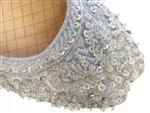 Silver silk Indian khussa shoes are covered with beads and sequins for women.
