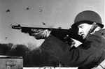 Photo of a GI firing a Tommy Gun from the World War 2 US Army training film Mastering the Thompson Sub Machine Gun.