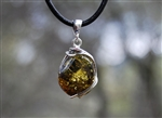 Amber pendant with green and gold tones set in an elegant silver setting.
