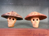 A clay skeleton skull smiling and wearing a big sun bonnet. Use as a paper weight or just a fun friend to watch you cook or gaurd your tequila collection.