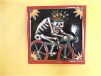 6 x 6 high fired Day of the Dead Tile of a skeleton riding a bike. This tile can be installed in an architectural Design Red border with black background.