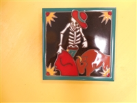 A 6 x 6 high fired Day of the Dead Tile. A skeleton Matador fights a Bull with his red cape. Teal Border and black background. This tile can be installed in an architectural Design