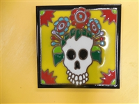 6 x 6 high fired Day of the Dead Tile. A white calavera full of red and blue flowers. Frida's eyebrows may have fallen off but she still has that all knowing smile. This tile can be installed in an architectural Design.Black border with yellow background.