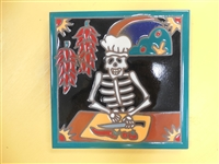 6 x 6 high fired Day of the Dead Tile. A white chefs hat sits on this skeletons head as he chops red peppers. This tile can be installed in an architectural Design.Teal border with black background.
