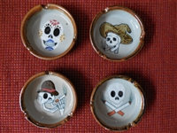 Four ceramic ashtrays from Mexico each with a different design calavera. One sports a brown derby hat, the other a tan worn out farming hat. The third is a skull and cigarette cross bones and the fourth is a sugar skull