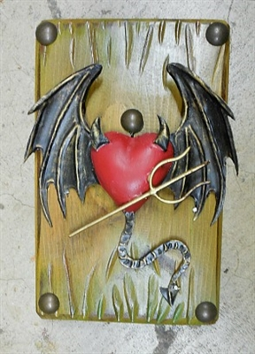 A winged flying tin Devil Heart with tail and fork. Framed by a rustic olive green frame and clavos