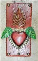 Green leaves grow out of a Mexican Tin Flaming Heart. Framed by a rustic orange frame and clavos