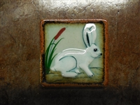 White Rabbit on both sides of a tile box candle. Assorted colors of wax. No scent