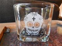A Square glass Votive. Measuring 3 1/2 x 3 1/2 inches has a Sugar Skull with cross etched on it and black beans in the bottom to accent and show off the design.