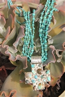 American made from New Mexico. A silver  and turquoise cross pendent with a long 31 inch matching stone neclace.