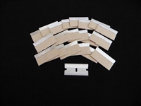 Large array of stainless steel single edge razor blades with paper edge protectors