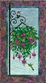 Quilt block of hummingbirds drinking nectar from a hanging plant.