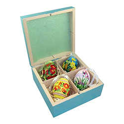 Set of 4 hand painted Polish chicken eggs (blown) in a hand painted display box.   This set is on sale due to what appears to be a pen line on the front left side of the box which can be seen in the first two pictures.   Each of the eggs has its own ribb