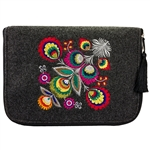 The IPad cover is made of stiff dark grey felt. The main decoration is vivid embroidery - Lowicz Flowers (made by Farbotka brand). Quilted lining and pocket inside. Cover is fastened with a zipper. Finished with a tassel.  Interior brand logo is slightly