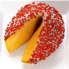 Giant fortune cookie dipped in dark chocolate and decorated with red hearts and white sprinkles.