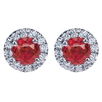 Shimmering red rubies fill in the center of these diamond and ruby stud earrings with a halo  in 14k white gold.