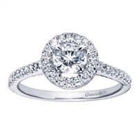 A round brilliant diamond halo sets up a bold round center diamond, accompanied by round brilliant diamonds all along the band of this white gold or platinum contemporary halo engagement ring.