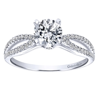 This rounded split shank engagement ring benefits from the glow of a round center diamond, featuring almost one quarter carats of round brilliant diamonds, available in white gold or platinum.