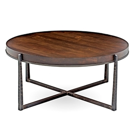 Pictured is the 54-inch diameter transitional style Cooper cocktail table with hand-forged iron base and thick wood slab table top from Charleston Forge.