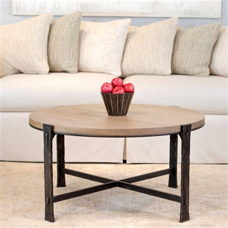 Pictured is the 48-inch round transitional style Woodland cocktail table with hand-forged iron base and wood slab table top from Charleston Forge.
