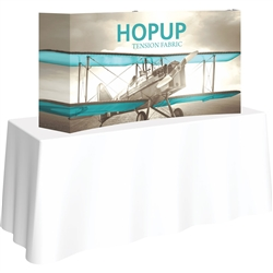 5ft Curved HopUp 2x1 Tabletop Fabric Trade Show Display with Full Fitted Graphic has a light weight, heavy duty frame that holds a fabric graphic mural. It sets up in seconds and can be packed away just as quickly after trade show or event
