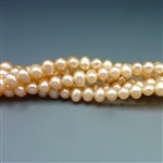 "5mm round peachy pink fresh water pearls, one 16"" strand"