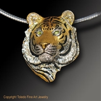 "Tiger Pendant ""I Am Tiger"" by wildlife artist and jeweler Daniel C. Toledo, Toledo Wildlife Works of Art is created entirely by Dan in his studio in sterling silver and then plated in rhodium and 22k gold, black enamel, and peridot eyes."