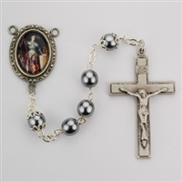 Saint Joan of Arc rosary has hematite beads, an image of St.  Joan of Arc for a rosary center and a pewter crucifix. Gift boxed.