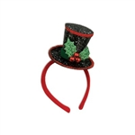 The Caroler Headband is a black sequined top hat decorated with holly leaves and berries. It is attached to the side of a standard headband covered in red felt. Top hat measures approx 3 inches high. One size fits most. One per package. No returns.