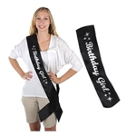 The Glittered Birthday Girl Satin Sash is black with Birthday Girl displayed in silver glittery writing. It is decorated with stars at both ends. Measures 33 inches long and 4 inches wide. One per package. No returns.