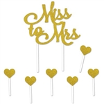 The Miss To Mrs Cake Topper is made of cardstock and printed on one side. Has gold glittered script lettering. Topper -4 in high and 4 1/2 in wide standing 8 1/2 in tall. Includes 6 1 in gold glittered hearts atop 31/2 stick. 7 pieces per package.