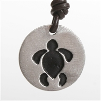 A contemporary design honu turtle pendant in Rhodium plated pewter. Comes with a Greek brown leather cord.Proudly Made In The U.S.A.All jewelry comes in an elegant gift box....