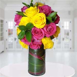 Two dozen yellow and pink roses bouquet in a glass vase.