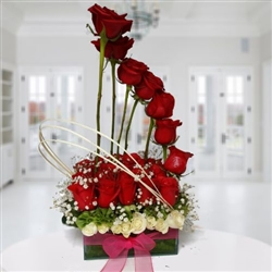 Two dozen red roses un glass vase. .