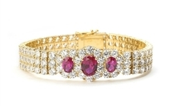 "7"" long Diamond Essence Bracelet with 2.0 Cts. Oval cut Ruby in center and 1.0 Ct. Ruby on each side encircled by Diamond Essence Stones making 3 rows all around wrist. Appx. 40.0 Cts. T.W. set in 14K Solid Yellow Gold."