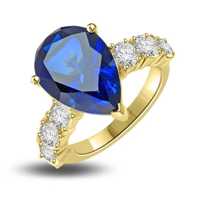 Diamond Essence Designer Ring with 5.50 cts. Pear Cut Sapphire Essence in center and three round stones on each side of center. 7.0 Cts. T.W. set in 14K Solid Yellow Gold.