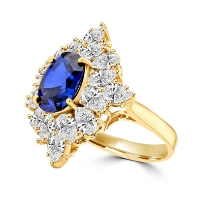 Designer ring with 3.5 Ct. oval Sapphire Essence set in four prongs, and surrounded by pear cut diamond essence stones in floral pattern. 8.5 Cts. T.W. et in 14K Solid Yellow Gold.