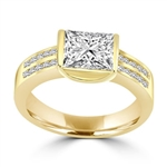 A unique East-West design, with a Channel Set 1.5 Ct. Radiant Emerald Cut Diamond Essence Centerand a bevy of Melee accents down the band for an exhilarting sensation in 14K Solid Gold.