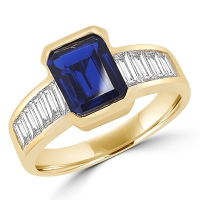 Escape with this Wide Band Ring with Channel Set Emerald Cut Sapphire Essence, 2.5 cts. separated by straight Diamond Bright Baguettes set vertically for a totally magnificent effect. 3.5 cts.T.W. set in 14K Solid Yellow Gold.