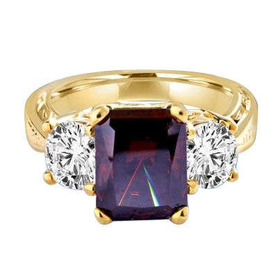 Finely crafted Chocolate Essence Emerald Cut Stone is flanked by saluting 1 Ct Round Brilliance. The band is ethnic and sexy! 6 Cts. T.W. set in 14K Solid Yellow Gold.