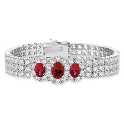 "7"" long Diamond Essence Bracelet with 2.0 Cts. Oval cut Ruby in center and 1.0 Ct. Ruby on each side encircled by Diamond Essence Stones making 3 rows all around wrist. Appx. 40.0 Cts. T.W. set in Platinum Plated Sterling Silver."