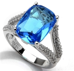 Diamond Essence Ring with 6 Ct. Blue Cushion Cut Stone and Melee on band, 6.15 Cts.T.W. in Platinum Plated Sterling Silver.