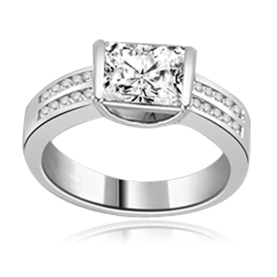 A unique East-West design, with a Channel Set 1.5 Ct. Radiant Emerald Cut Diamond Essence Center and a bevy of Melee accents down the band for an exhilarting sensation, in Platinum Plated Sterling Silver.