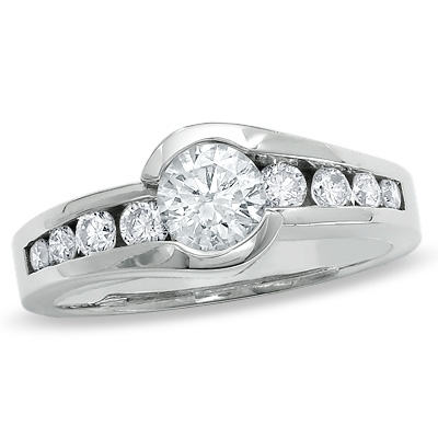 Designer Ring with channel set, 1.0 Cts. Round Brilliant Diamond Essence in center accomapnied by graduating melee on either side, 1.30 Cts. T.W. set in Platinum Plated Sterling Silver.