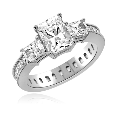 Diamond Essence Ring with Radient Emerald Center Followed by Princess cut Stones And Round Brilliant Melee on the band, 4.50 Cts.T.W. set in Platinum Plated Sterling Silver.
